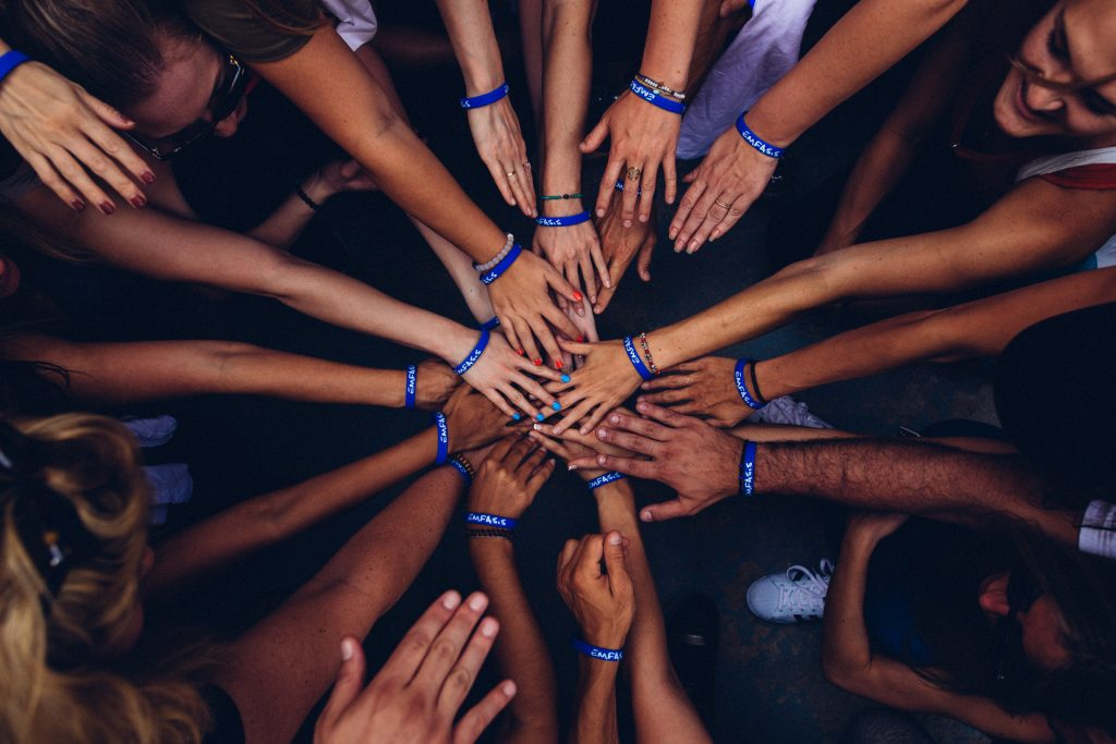 Hands brought together in a huddle