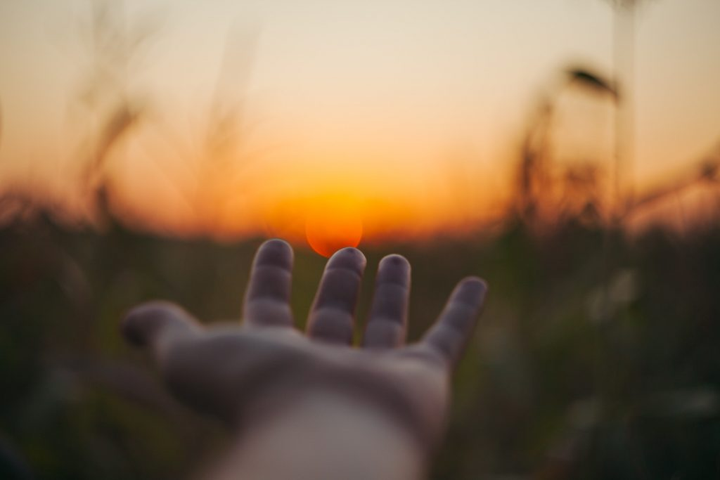 Hand reaching out for sunset